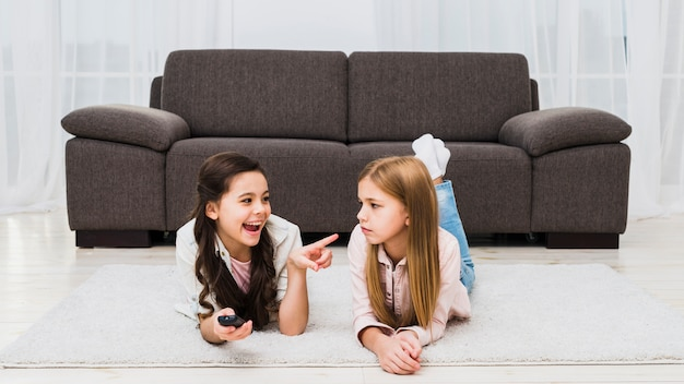 Girl making mischief of her friend lying on carpet at home