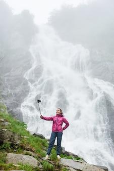 Девушка фотографируется у водопада