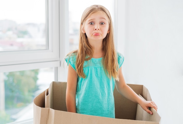 Girl making sad grimace inside the box