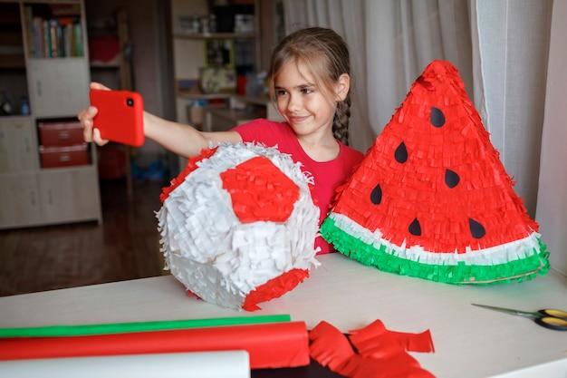 Девушка делает селфи из пиньяты своими руками из картона и цветной крепированной бумаги, чтобы поделиться им в социальных сетях