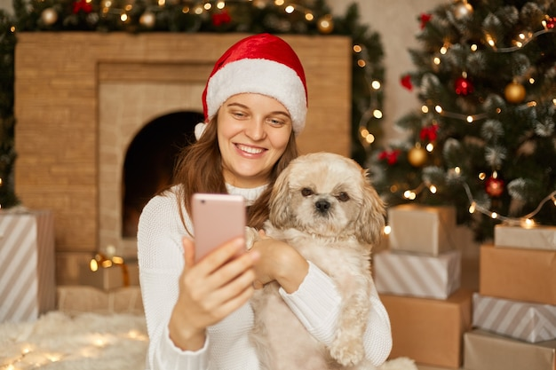 Girl making selfie with nice puppy while sitting in festive room with fireplace and x-mas tree, girl looks at mobile phones's screen with charming smile, wearing santa hat and casual jumper.