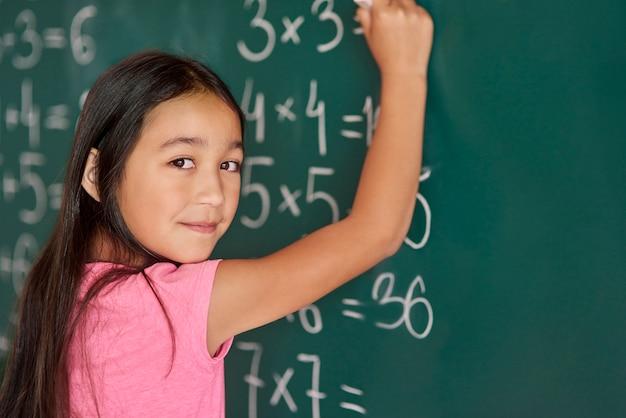 黒板でいくつかの運動をしている女の子