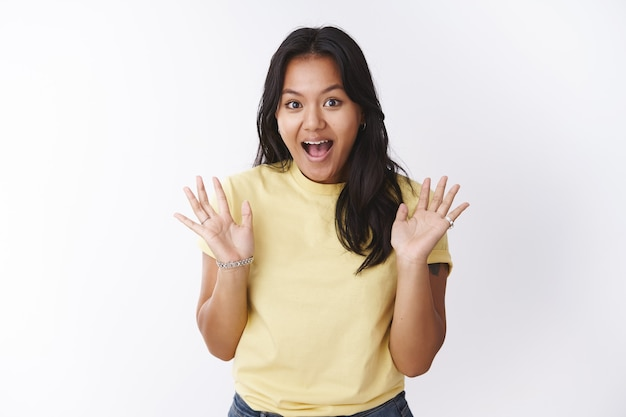 Girl making surprise arriving secretly to friend house yelling hello and waving raised palms joyfully posing upbeat and joyful with enthusiastic expressions against white background in yellow t-shirt