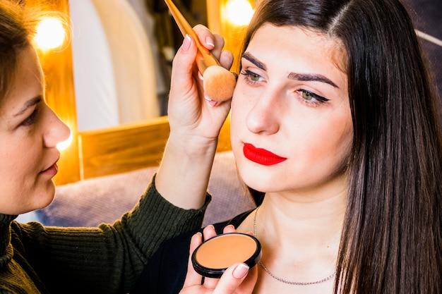 Girl making up her cheeks
