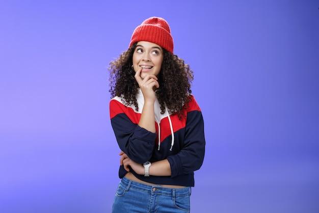 눈사람이 무엇을 만들었는지 생각하는 소녀, 생각하는 것처럼 손가락을 물어뜯는 사려깊은 표정으로 귀엽고 어리석은 생각을 하고, 기뻐하고, 모자와 따뜻한 스웨터를 입고 흥미로운 생각을 하고 있습니다.