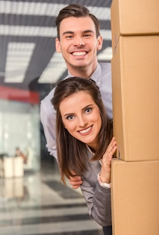 A girl and a man peeking out from behind a box and smiling.