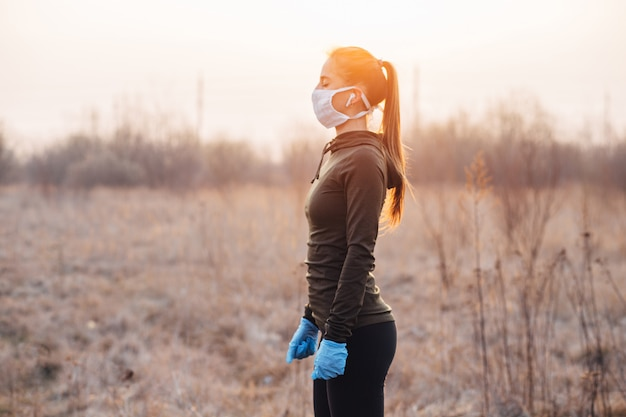 Girl in mask and blue gloves during quarantine went out to run