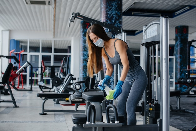 The girl in the mask disinfecting the gym equipment during a pandemic.