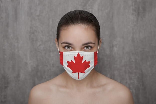 A girl in a mask on her face with a canadian flag