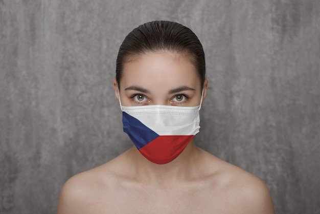 A girl in a mask on her face with the flag of the czech republic