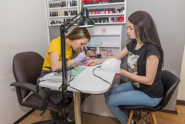 Девушка-мастер делает клиентке маникюр в маникюрном салоне. мастер покрывает ногти красным лаком. концепция ухода за ногтями