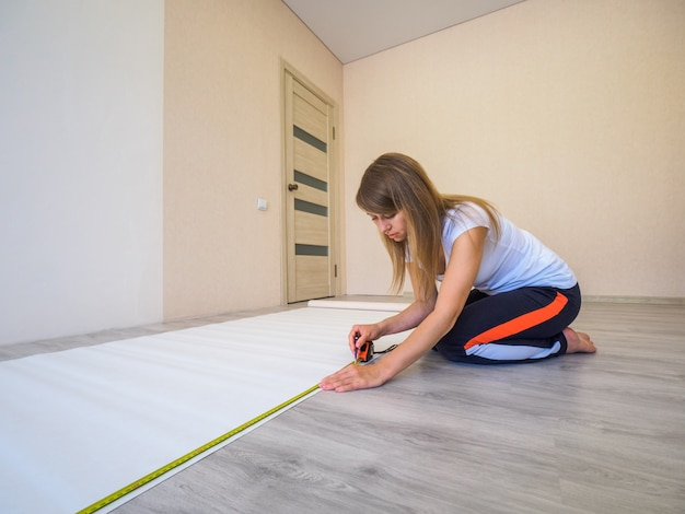Girl measures the length of the strip of wallpaper