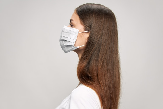 Girl in a medical face mask in side view