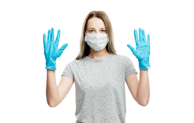 A girl in a medical mask and blue gloves raised her hands up. precautions during coronavirus rendezvous. isolated on a white wall.