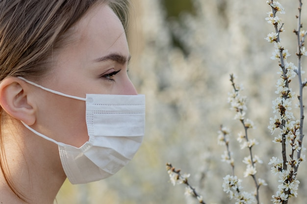 Girl in a medical mask. girl in the spring among the blooming garden. a girl in a protective medical mask. spring allergy concept
