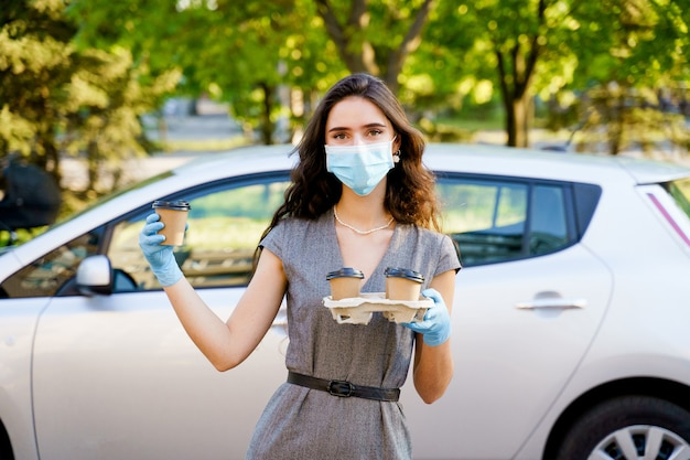 Girl in medical mask and gloves holds tray of disposable coffee cups