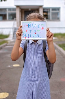 Girl in medical mask holds picture with back to school message offline and social distance rules