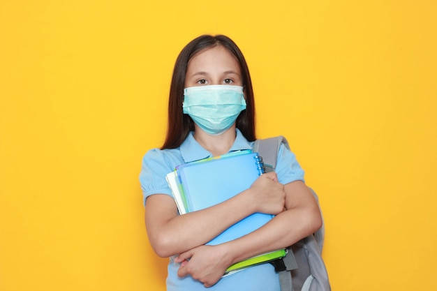 Girl in medical mask hugs textbooks on yellow background back to school space for advertising