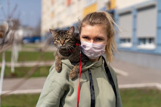 A girl in a medical mask is walking with a cat along the street near the house
