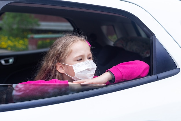 A girl in a medical mask looks out the open window of a white car.