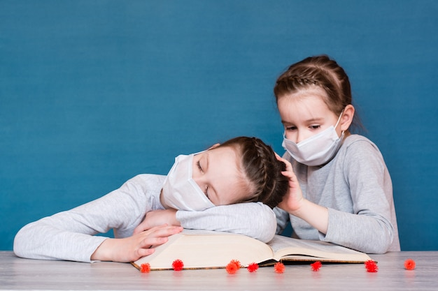 A girl in a medical mask in quarantine sleeps on a book, and another girl in a mask is afraid of the virus and wakes her up.