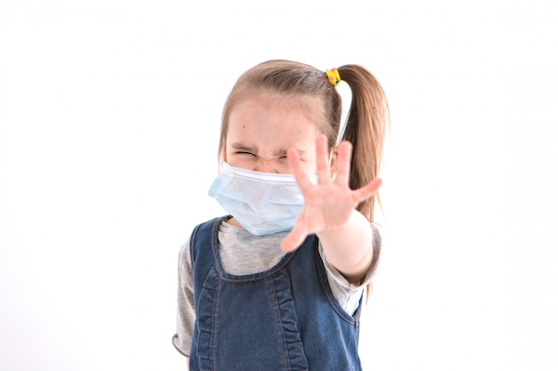A girl in a medical mask says stop infection. the child put his hand forward. prevention of the disease. isolated on white wall