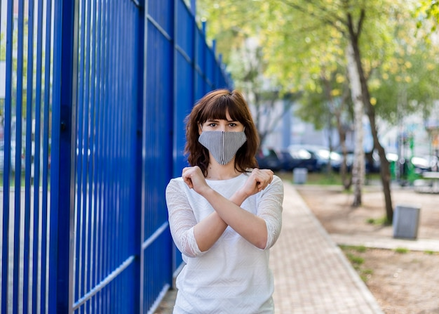 A girl in a medical mask stands on the street with her arms crossed. a young brunette girl shows a forbidding sign with her hands