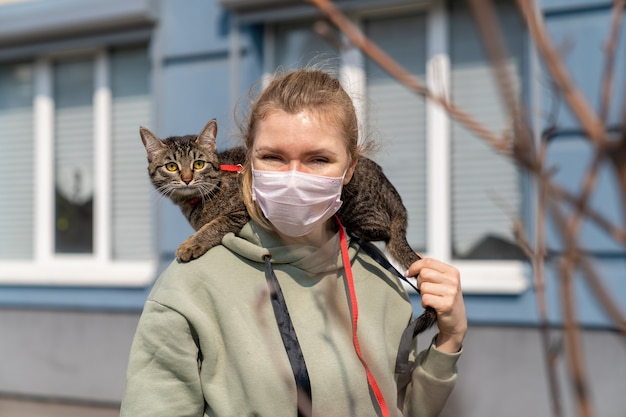 A girl in a medical mask walks along the street with a cat