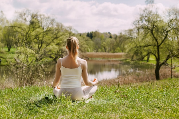 A girl meditates in the lotus position in the fresh air in the park.