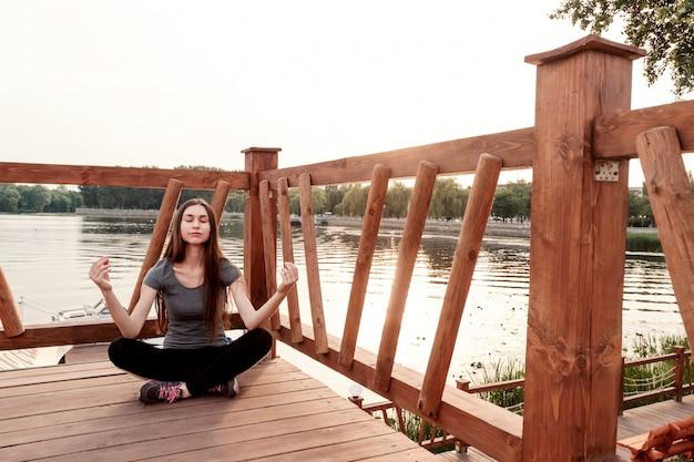 女の子は早朝に水の近くで瞑想します。スポーツ、健康的なライフスタイル、ボディケアの概念。