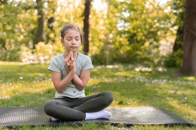ヨガマットで瞑想する女の子