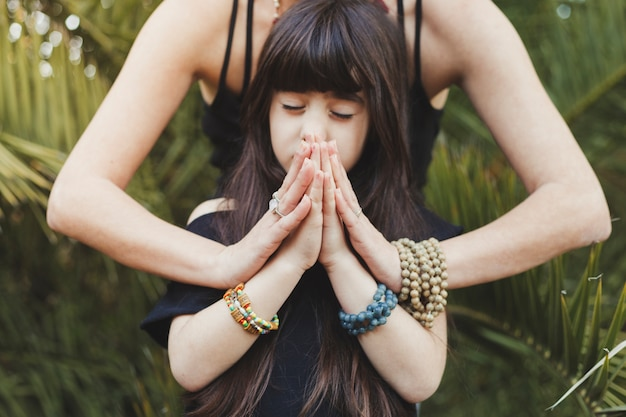 Girl meditating with mother