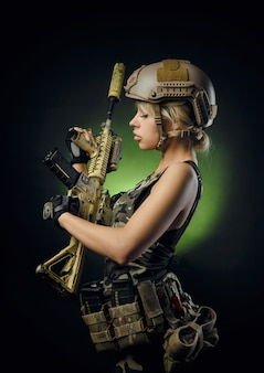 Girl in military overalls airsoft posing with a gun in her hands