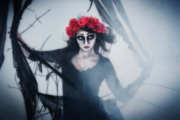 Girl mime in fog in forest, halloween. a wreath of flowers on head of woman, dark scary woods