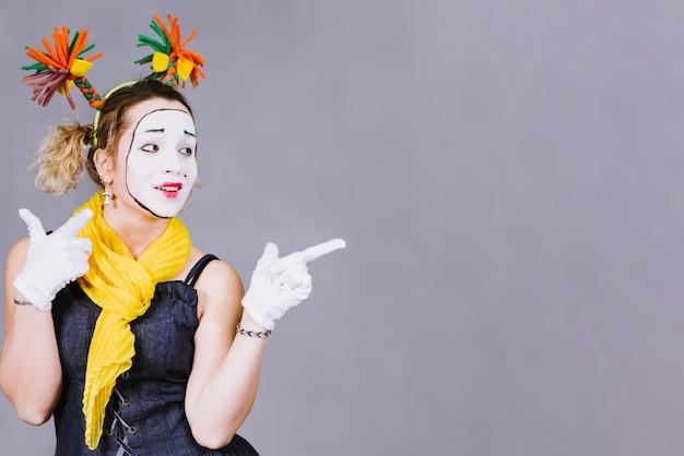 Girl mime posing near a gray
