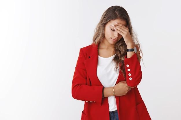 Девушка упустила удачный шанс, сожалея, делая жест фейспалма, держась за лоб, глядя вниз, мрачно расстроенная, грустная, измученная, столкнувшись с неудачей, стоя, разочарованная белая стена