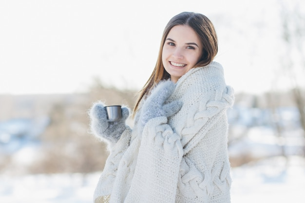 Girl in mittens and a blanket drinking hot tea