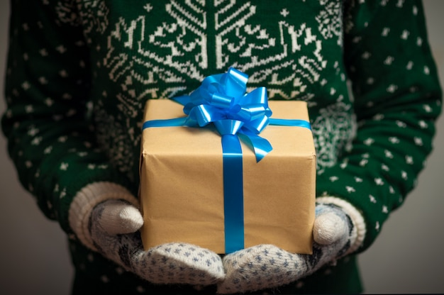 Girl in mittens and a sweater with a winter ornament holds christmas gifts