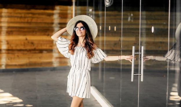 ドレスと帽子の女の子モデルが店に行きます。