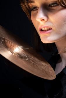 검은색 옷을 입은 소녀 모델 음악가가 스네어 드럼 심벌즈를 들고 옆을 바라보고 있습니다. 검정색 배경에.