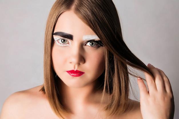 短い髪型と黒と白の眉毛を持つ少女モデル。