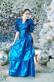 Девушка-модель с голубыми глазами в синем праздничном платье позирует на фоне блестящих новогодних украшений в виде елки и зеркальных шаров
