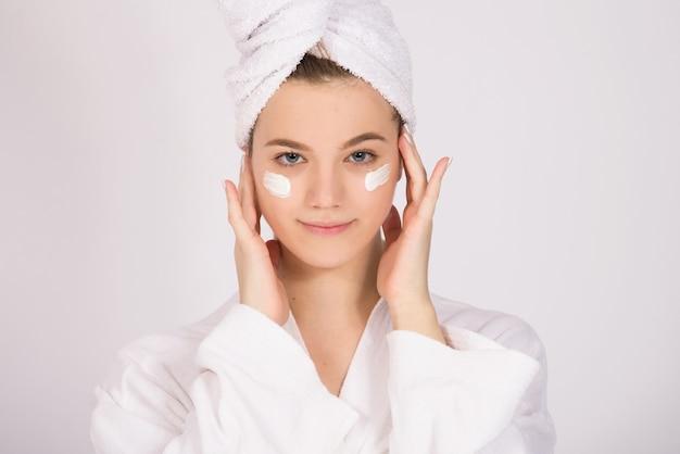 그녀의 머리에 얼굴 크림과 수건, 피부 노화 관리 및 피부 제품의 개념, 복사 공간 흰색 배경에 소녀 모델