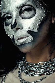 어두운 배경에 실버 마스크 해골 페인트로 소녀 모델