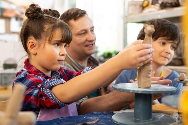Girl modeling clay animal near teacher and brother