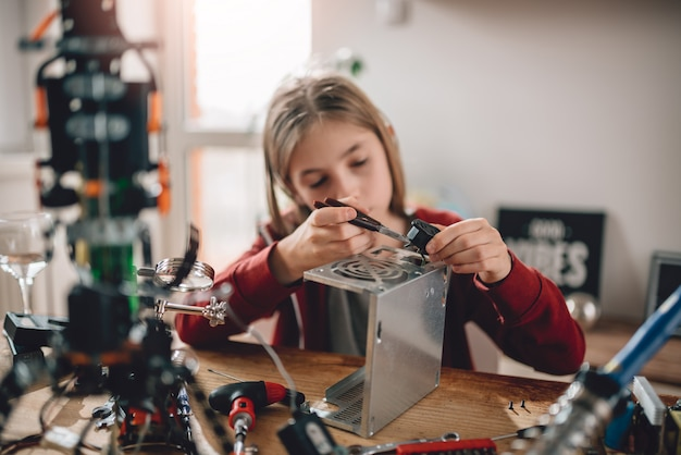 Girl modifying power supply and  learning robotics