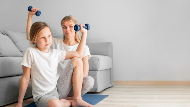 Girl and mom exercise with weights
