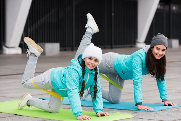Girl and mom training with elastic bands on mat
