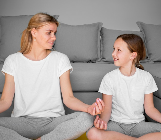 Girl and mom in yoga pose looking at each other