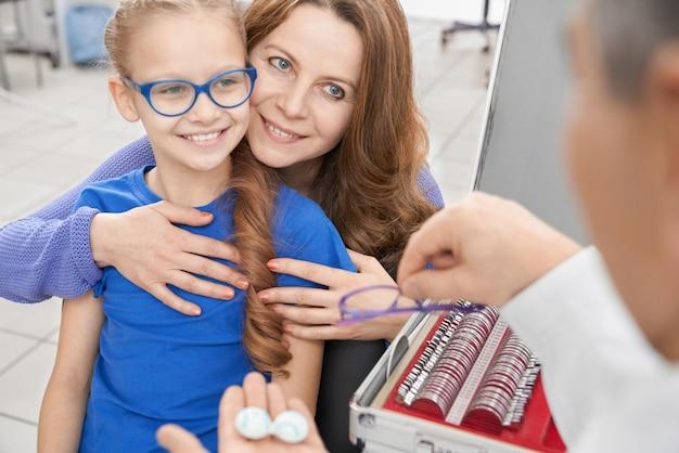Girl and mother choosing eye lenses or glasses.